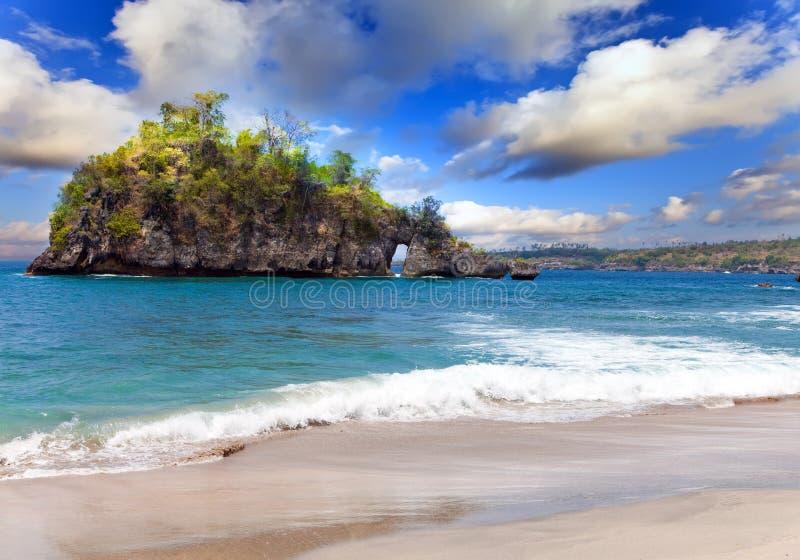 Sandy Beach em rochas no oceano. Indonésia, fotografia de stock