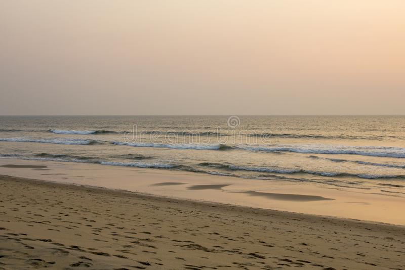 A sandy beach with footprints on the background of the sea under a gray pink blue evening sunset sky stock photo