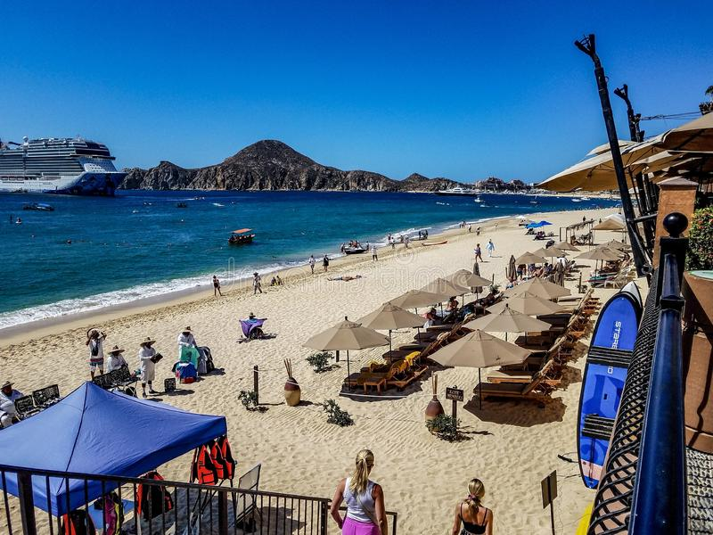The sandy beach in front of the hotels in Cabo San Lucas with the Peninsula and a cruise ship on a clear, sunny day royalty free stock image