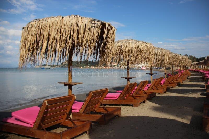 Sandy Beach With Local Palm lämnar paraplyet royaltyfri fotografi