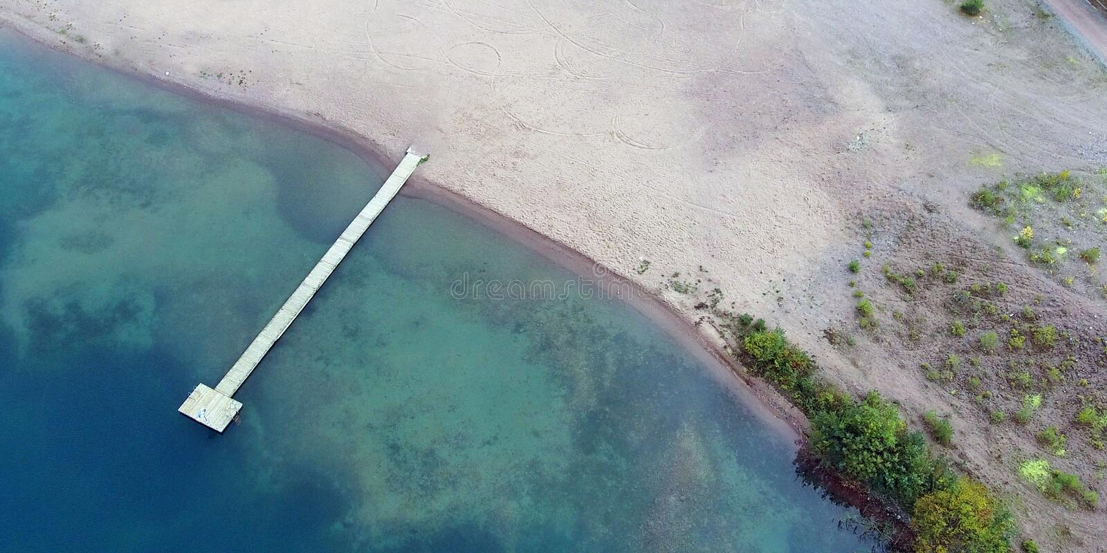 Sandy beach with long wooden pier from above royalty free stock photography