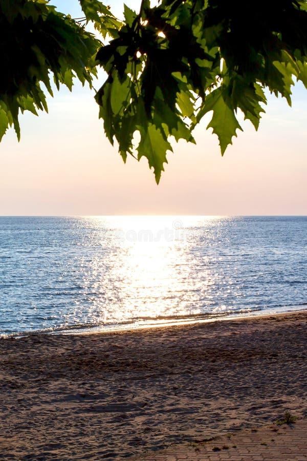 Sandy Beach, mar durante o fundo do por do sol foto de stock