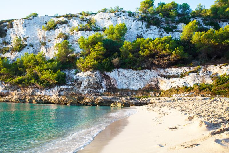 Sandy Beach na baía bonita com água do mar dos azuis celestes foto de stock