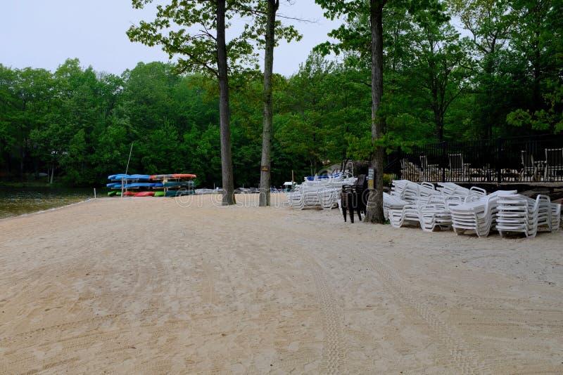 Sandy Beach på sjön med fartyg och staplade stolar royaltyfria bilder