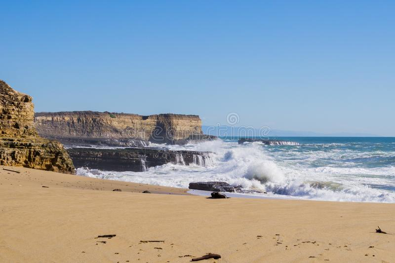 Sandy beach on the Pacific Ocean Coast during high tide and strong surf, Wilder Ranch State Park, California royalty free stock photo