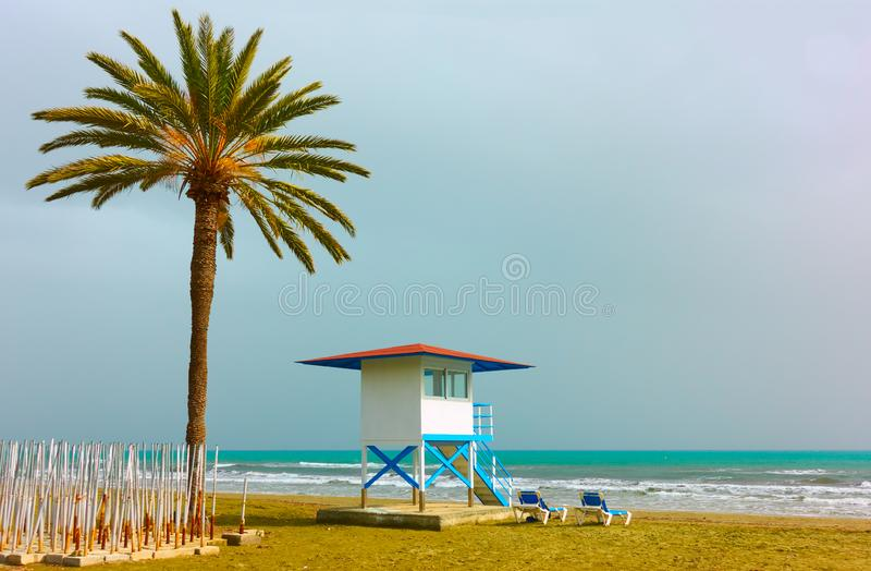 Sandy beach with palm tree and life guard tower stock photography