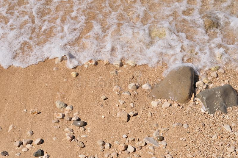 Sandy beach with pebbles and wave stock photography
