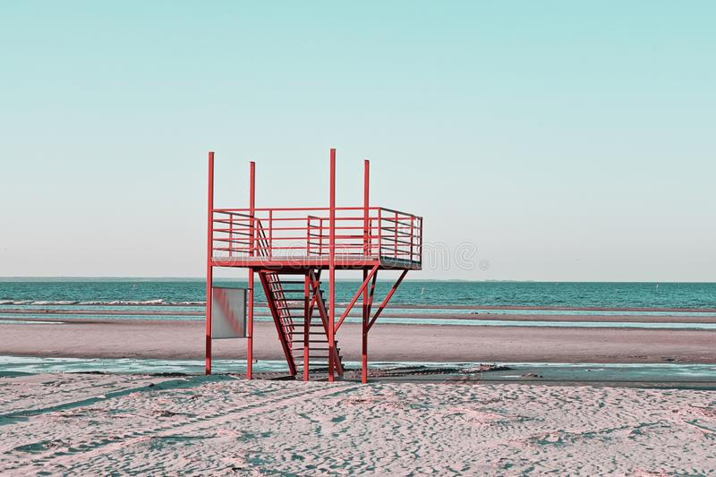 Sandy beach with red vintage lifeguard station royalty free stock images