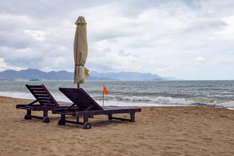Sandy Beach só com cadeiras e guarda-chuvas de praia perto do mar fotografia de stock royalty free