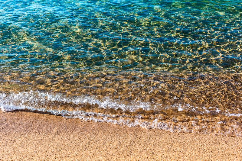 Sandy beach of sea. Transparent turquoise water, soft wave, sunlight reflecting on sea bottom stock images
