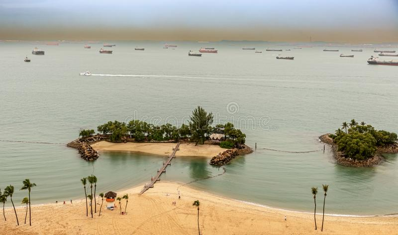Sandy beach on Sentosa island in Singapore. Aerial view at sandy beach on Sentosa island in Singapore at the horizon are cargo ships passing thru strait of stock photography