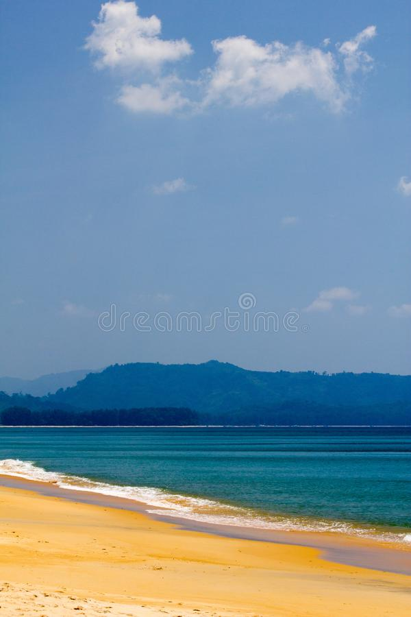 Vertical view of a sandy beach. Sandy beach with small waves. the sea water forms layers of blue and turquoise on a lightly cloudy day. looks like an island stock photos