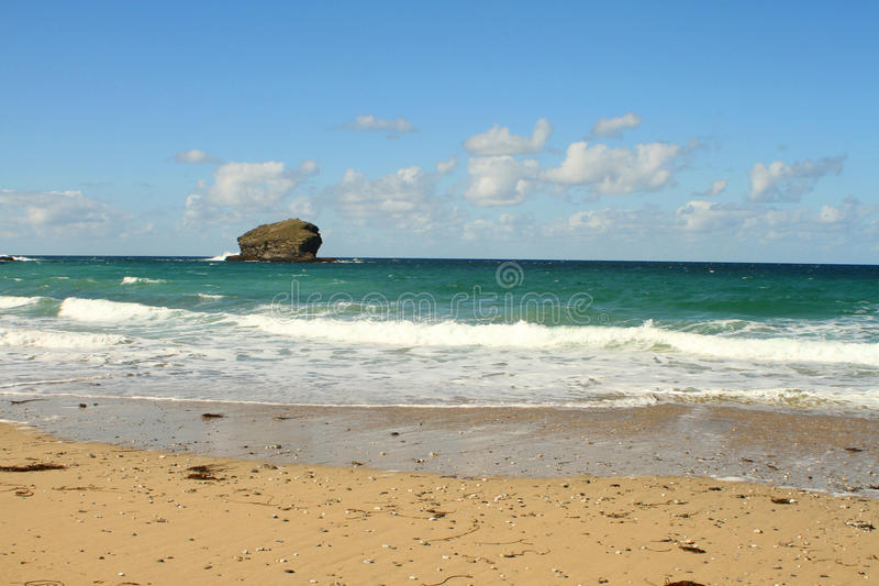 Sandy beach with tall rock. Bright Summer sky and turquoise blue water stock photo