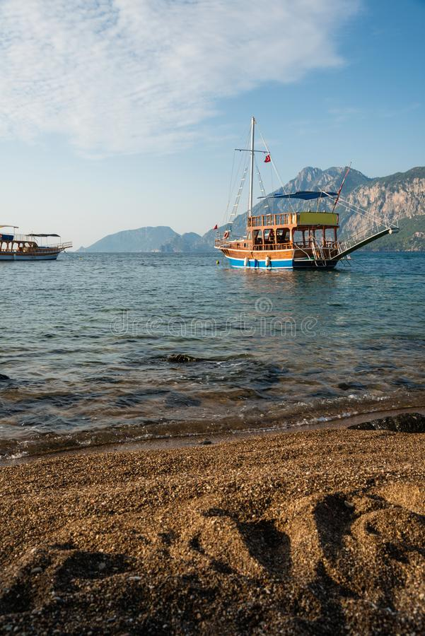 Sandy beach and touristic boats in Turkey. Sandy beach and touristic boats, Turkey coastline royalty free stock images