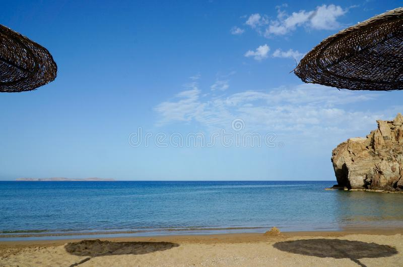 The sandy beach from under sun-wattled umbrellas stock photography