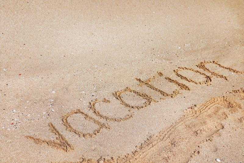 Sandy beach with written word Vacation on sunny day. royalty free stock image