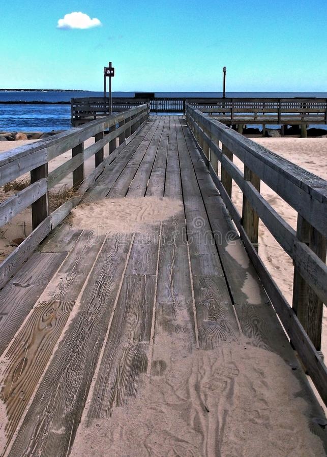 Sandy boardwalk leading to beach and pier. stock photo
