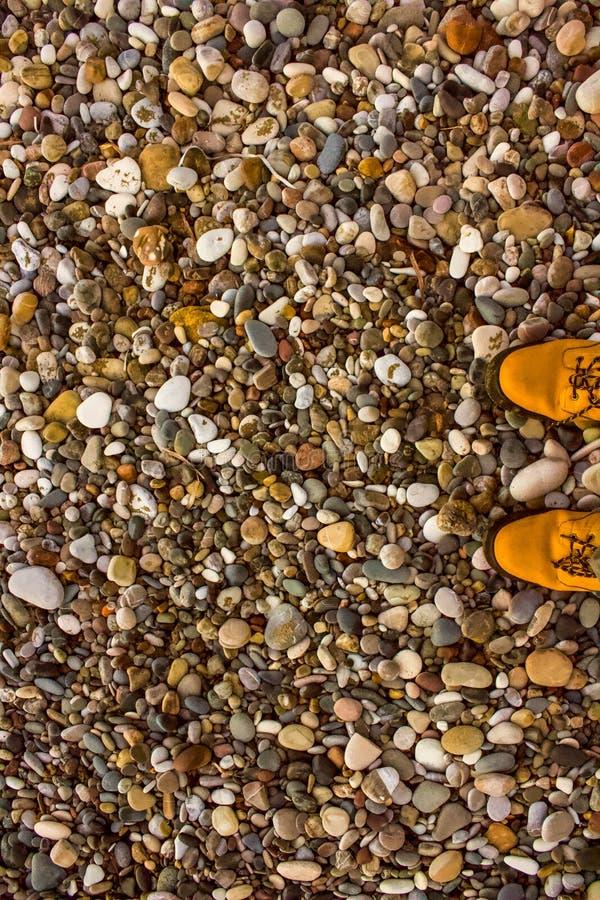 Sandy Boots en multicoloured kiezelstenen royalty-vrije stock afbeeldingen