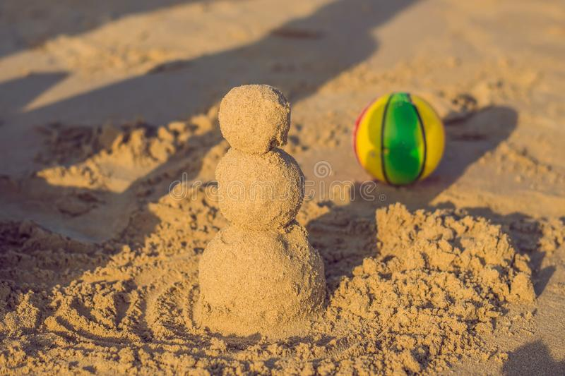 Sandy christmas snowman in red santa hat and sunglasses at sunny beach. Holiday concept for New Years Cards royalty free stock image
