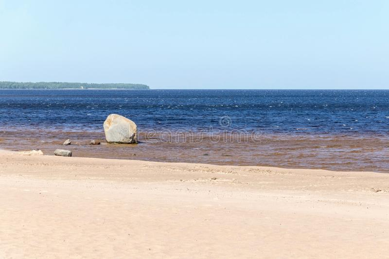 Sandy coast of the sea gulf with one stone. The sandy coast of the sea gulf with one stone and with the line of the horizon on blue water and the sky stock image