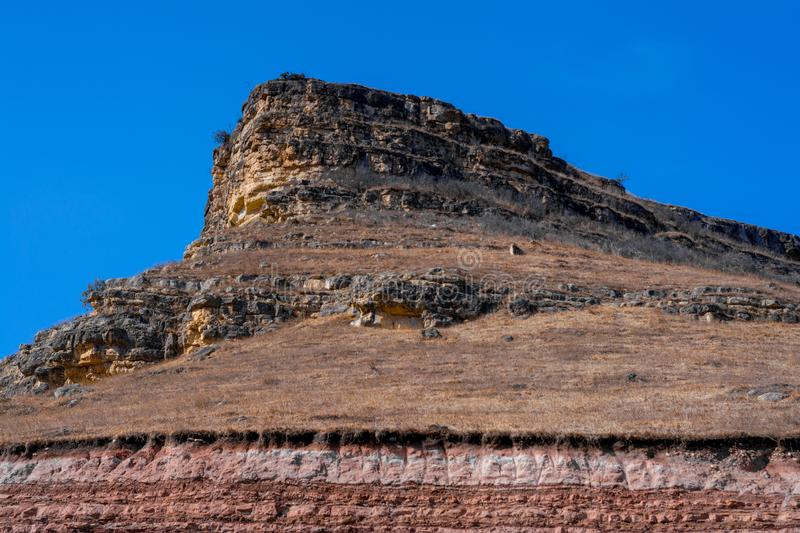 Sandy mountain with a sharp cliff and a small amount of vegetation against the blue sky. Canyon, travel, sandstone, panorama, view, attractions, breeds, color stock photos