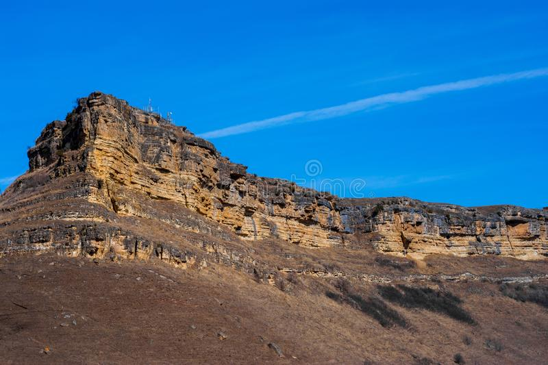 Sandy mountain with a sharp cliff and a small amount of vegetation against the blue sky. Canyon, travel, sandstone, panorama, view, attractions, breeds, color royalty free stock photos