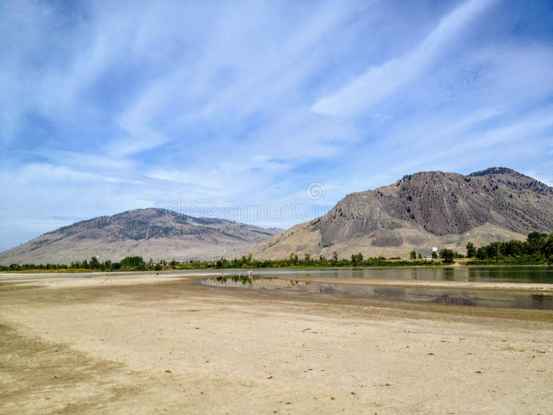 The sandy river bank of the North Thompson river in the beautiful dry landscape of Kamloops, British Columbia, Canada. A great spot for locals walk go swimming stock images