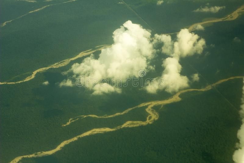 A sandy river beds among a green forest, view from a great height. white clouds above the ground. aerial photography royalty free stock images