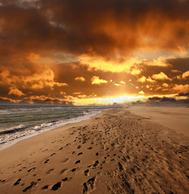 Sandy sea beach with footprints on dramatic sky stock images