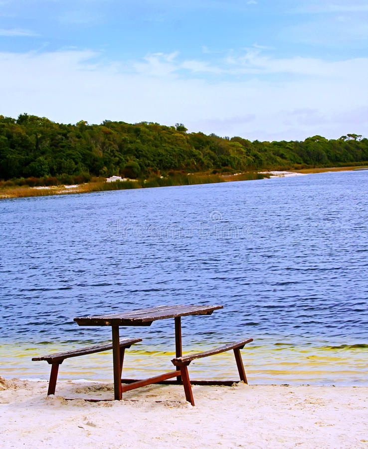 On the Sandy Shore. Weathered picnic table on the sandy shore of a remote lagoon stock photos