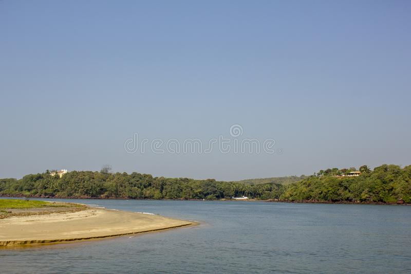 A sandy shore on the background of the river and hills with green trees and houses under a clear blue sky stock images