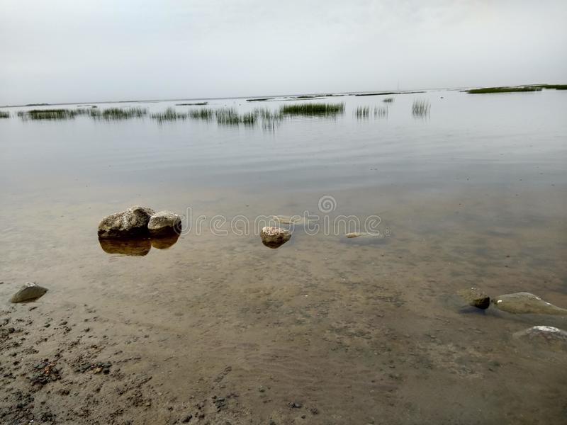 Sandy shore of the Bay. In the spring, gloomy weather, clouds, water, stones, sand, clear water royalty free stock photography