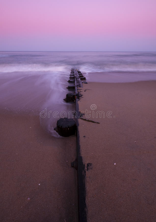 Sandy shore at dawn. With pilings going into ocean royalty free stock images