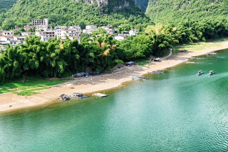 Sandy shore of the Li River and parked tourist rafts. View of sandy shore of the Li River (Lijiang River) and parked tourist motorized rafts at Yangshuo County stock photos