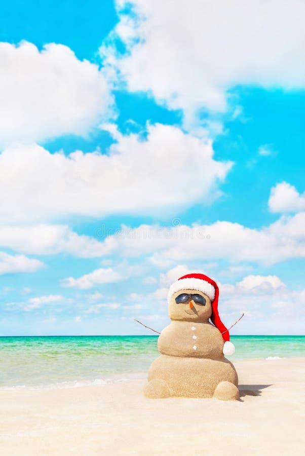 Sandy snowman in santa hat at beach. Christmas concept royalty free stock photos