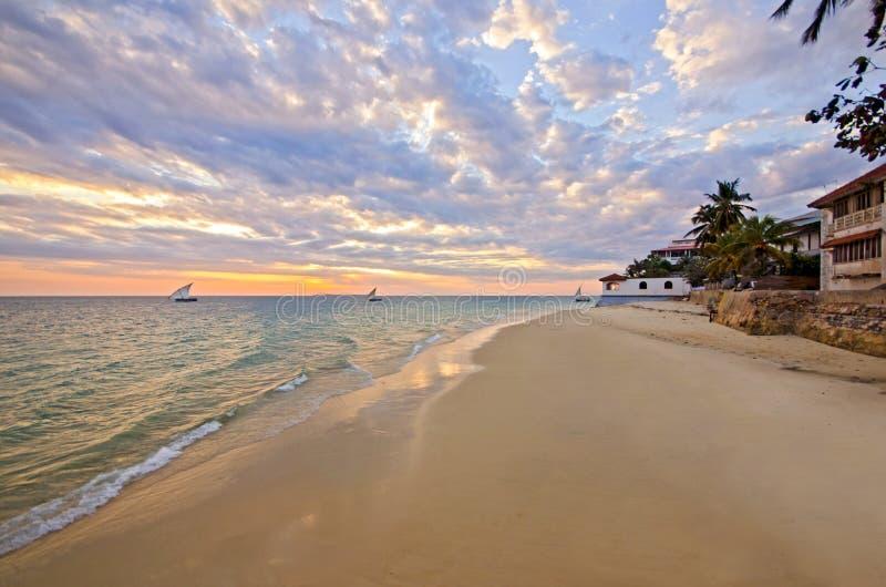 Sandy-Strand mit Boot und Sonnenuntergang auf Zanzibar stockfotos