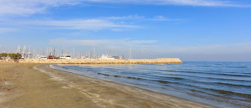 Sandy-Strand mit entfernter Ansicht von Larnaka-Jachthafen in Zypern Wolkenhintergrund des blauen Himmels und des Weiß lizenzfreies stockfoto
