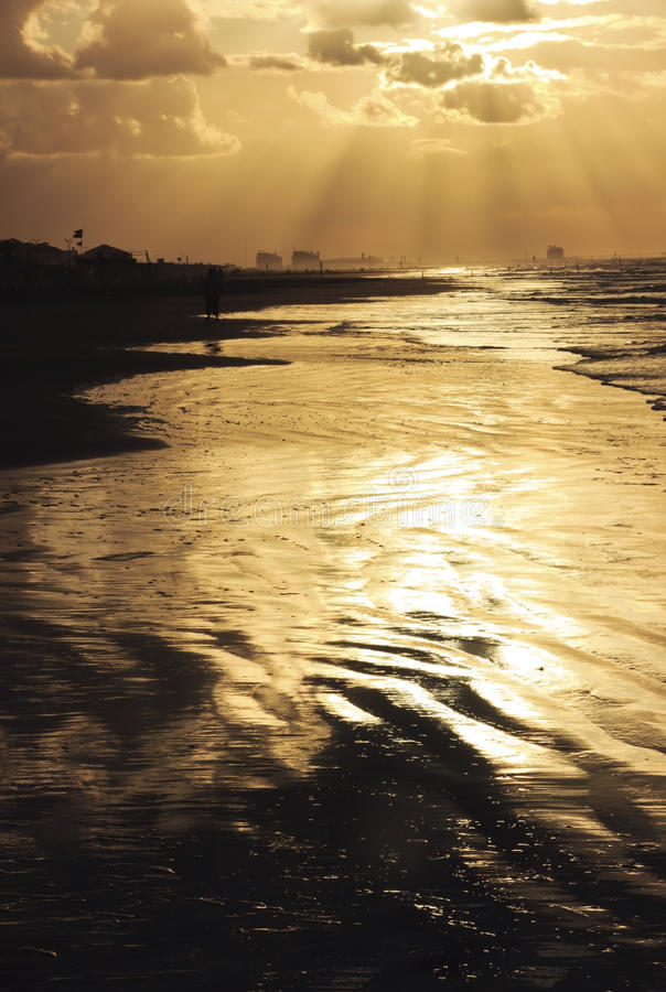 Sandy-Strand mit Wellen und goldenem Sonnenuntergang lizenzfreies stockbild