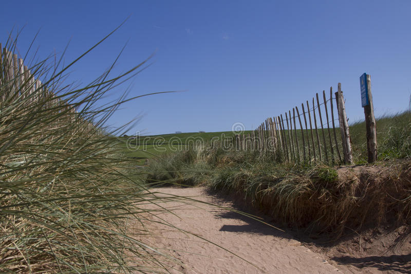 Sandy walk to Thurlestone beach Devon. Green hills in background royalty free stock images