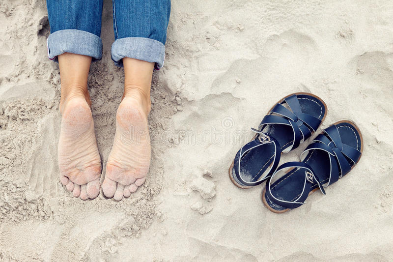 Sandy woman feet and pair of shoes. Relaxed sandy young woman feet and pair of shoes on the beach royalty free stock photo