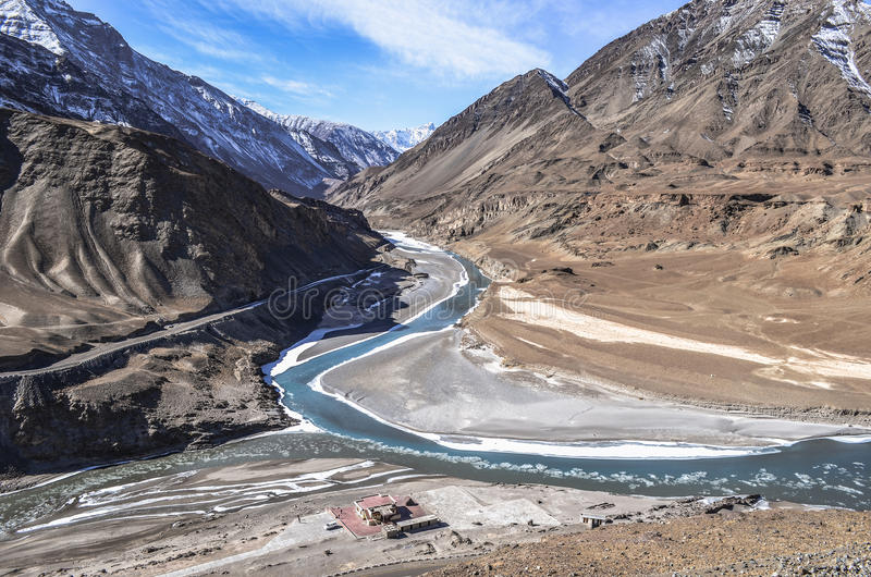 Meeting point. Mysterious zanskar meets the mighty Indus enroute its journey giving a perfect glimpse of two different coloured rivers coming together at a stock photo
