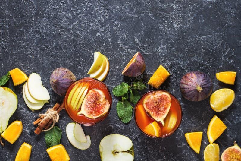 Sangría con las manzanas, naranja, higos, uvas, menta de la fruta del cóctel en la tabla de piedra imagen de archivo libre de regalías