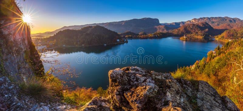 Sangrado, Eslovênia - o nascer do sol bonito do outono no lago sangrou em um tiro panorâmico com a igreja da peregrinação da supo imagens de stock royalty free