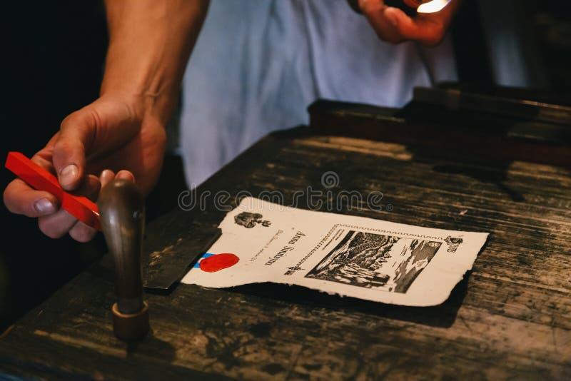 Sangrado, Eslovênia - setembro, 8 2018: Perto acima das mãos do homem que fazem uma lembrança só, derretendo uma vela vermelha da fotografia de stock