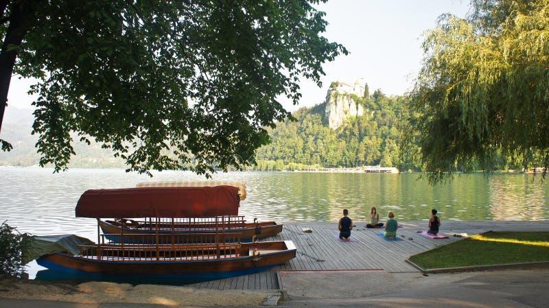 Sangrado, Eslovênia - 07 19 2015: Vista bonita do lago e o castelo, o Julian Alps e os barcos, manhã ensolarada, pessoa que faz a imagem de stock royalty free