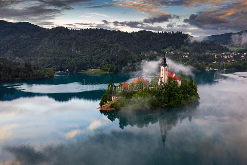 Sangrado, Eslovenia - mañana de niebla mágica en Blejsko sangrado lago Jezero con la iglesia del peregrinaje de la suposición de  fotos de archivo libres de regalías