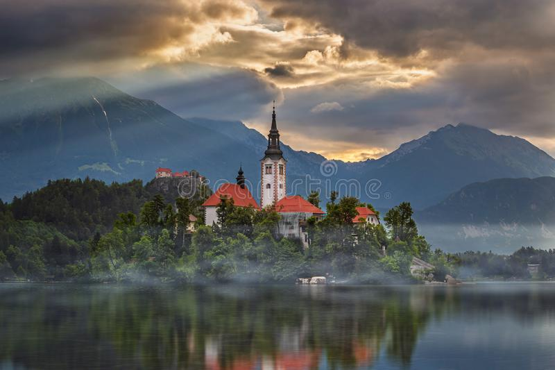 Sangrado, Eslovenia - salida del sol brumosa en Blejsko sangrado lago Jezero con la iglesia del peregrinaje de la suposición de M imagenes de archivo