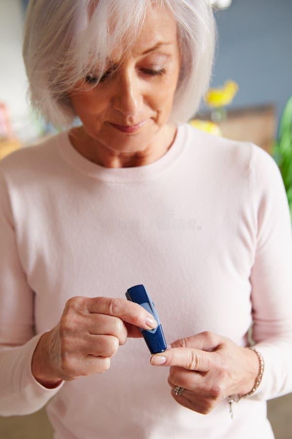 Sangre de comprobación diabética femenina mayor Sugar Levels imagen de archivo