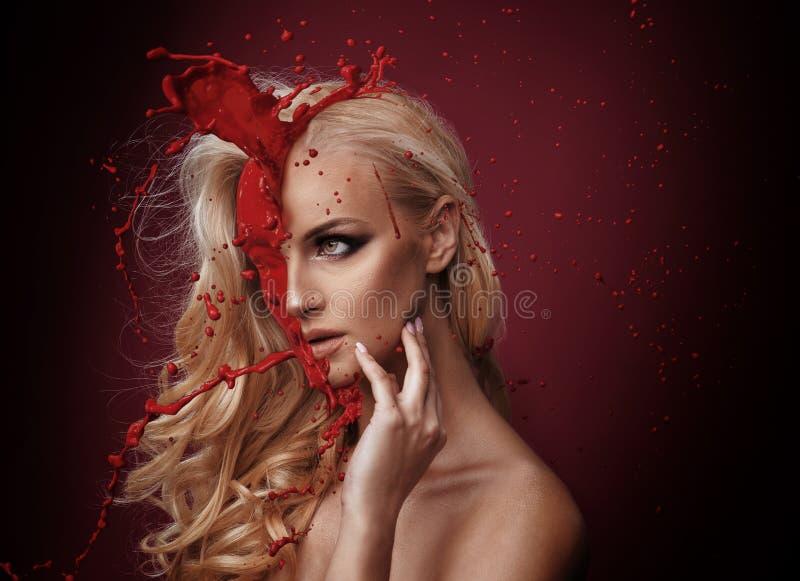 Sangue che spruzza sul fronte di una donna beuatiful immagine stock