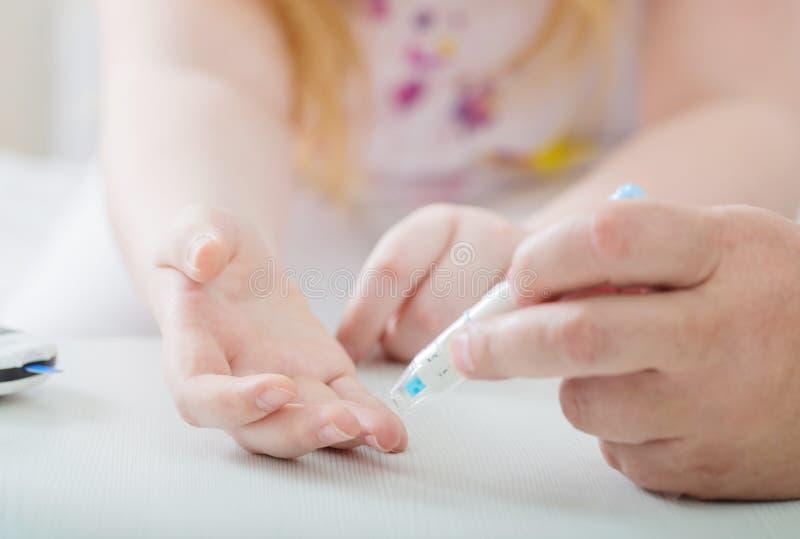 Sangue de medição Sugar Level Of Girl With Glucometer imagem de stock royalty free